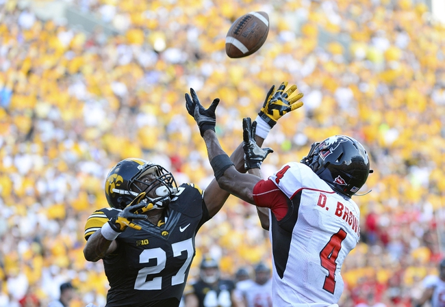 Aug 31, 2013; Iowa City, IA, USA; Northern Illinois Huskies wide receiver Da'Ron Brown (4) attempts to make a catch against Iowa Hawkeyes defensive back Jordan Lomax (27) during the fourth quarter at Kinnick Stadium. Northern Illinois defeats Iowa 30-27. Mandatory Credit: Mike DiNovo-USA TODAY Sports