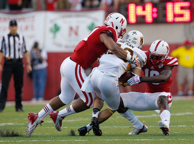 Aug 31, 2013; Lincoln, NE, USA; Nebraska Cornhuskers defenders David Santos (41) and Stanley Jean-Baptiste (16) tackle Wyoming Cowboys receiver Dominic Rufran (33) in the first half at Memorial Stadium. Mandatory Credit: Bruce Thorson-USA TODAY Sports
