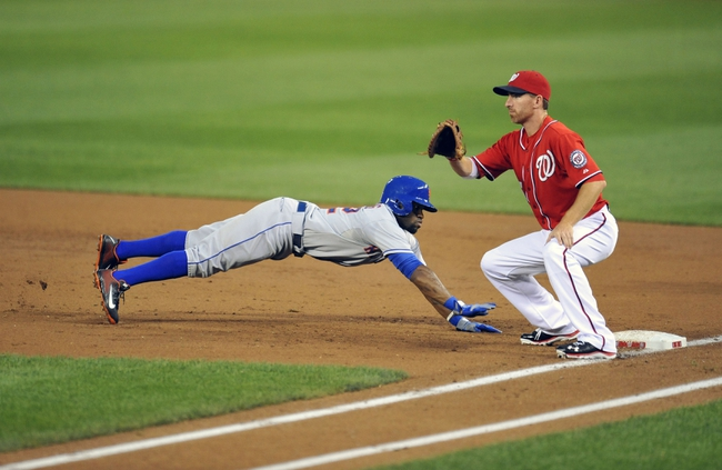 Aug 31, 2013; Washington, DC, USA; New York Mets left fielder Eric Young (22) dives back to first base safely in the third inning as Washington Nationals first baseman Adam LaRoche (25) does not get the throw in time at Nationals Park. Mandatory Credit: Joy R. Absalon-USA TODAY Sports
