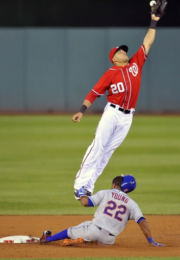 Aug 31, 2013; Washington, DC, USA; New York Mets left fielder Eric Young (22) steals second base safely as Washington Nationals shortstop Ian Desmond (20) cannot handle the throw in the third inning at