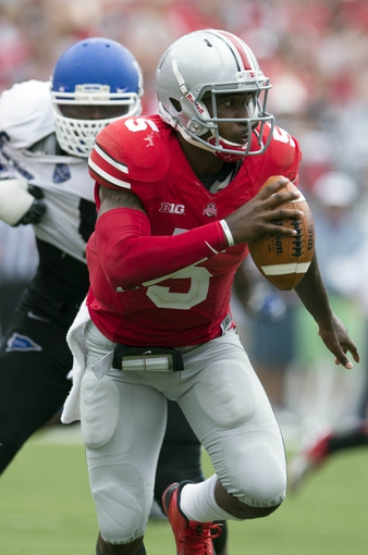 Aug 31, 2013; Columbus, OH, USA; Ohio State Buckeyes quarterback Braxton Miller (5) tries to evade pressure from Buffalo Bulls linebacker Khalil Mack (46) at Ohio Stadium.  Ohio State won the game 40-20. Mandatory Credit: Greg Bartram-USA TODAY Sports