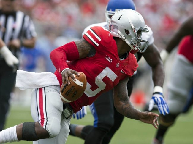 Aug 31, 2013; Columbus, OH, USA; Ohio State Buckeyes quarterback Braxton Miller (5) tries to evade pressure from Buffalo Bulls linebacker Khalil Mack (46) at Ohio Stadium. Ohio State won the game 40 Mandatory Credit: Greg Bartram-USA TODAY Sports