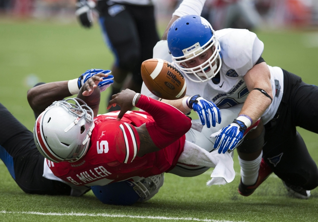 Aug 31, 2013; Columbus, OH, USA; Ohio State Buckeyes quarterback Braxton Miller (5) loses the ball as he is tackled by Buffalo Bulls linebacker Khalil Mack (46) and linebacker Blake Bean (33) at Ohio Stadium. The play was nullified on a Buffalo Bulls penalty.Ohio State won the game 40-20. Mandatory Credit: Greg Bartram-USA TODAY Sports