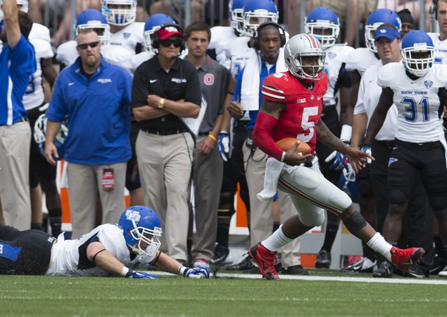 Aug 31, 2013; Columbus, OH, USA; Ohio State Buckeyes quarterback Braxton Miller (5) evades a tackle attempted by Buffalo Bulls linebacker Blake Bean (33)  at Ohio Stadium.  Ohio State won the game 40-20. Mandatory Credit: Greg Bartram-USA TODAY Sports