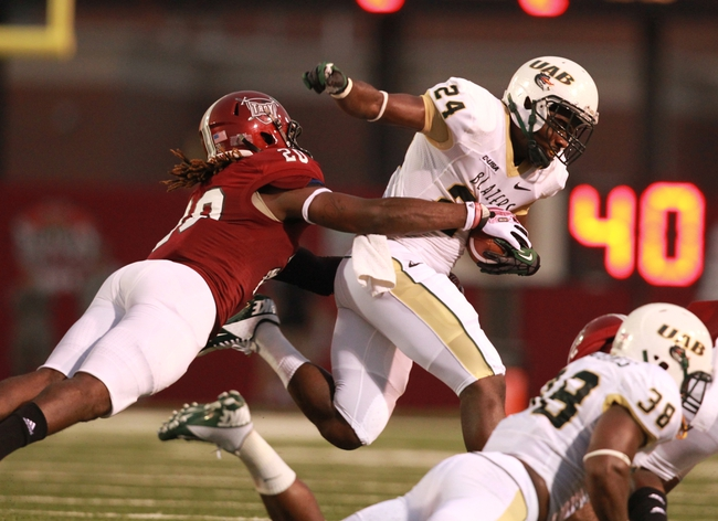 Aug 31, 2013; Troy, AL, USA;  UAB Blazers running back Greg Franklin (24) is grabbed by Troy Trojans linebacker Terris Lewis (20) at Veterans Memorial Stadium. Mandatory Credit: Marvin Gentry-USA TODAY Sports