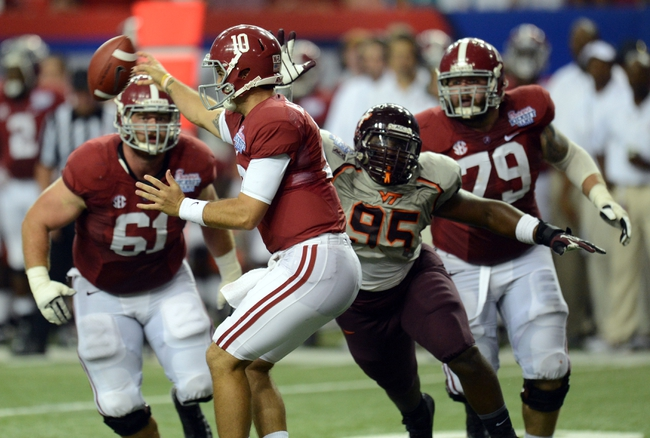 Aug 31, 2013; Atlanta, GA, USA; Alabama Crimson Tide quarterback AJ McCarron (10) throws under pressure from Virginia Tech Hokies defensive tackle Nigel Williams (95) during the fourth quarter of the 2013 Chick-fil-A Kickoff game at the Georgia Dome. Mandatory Credit: Dale Zanine-USA TODAY Sports