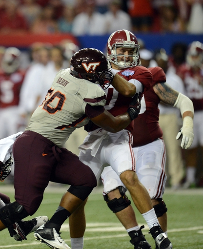 Aug 31, 2013; Atlanta, GA, USA; Virginia Tech Hokies linebacker Jamieon Moss (50) tackles Alabama Crimson Tide quarterback AJ McCarron (10) during the fourth quarter of the 2013 Chick-fil-A Kickoff game at the Georgia Dome. Mandatory Credit: Dale Zanine-USA TODAY Sports