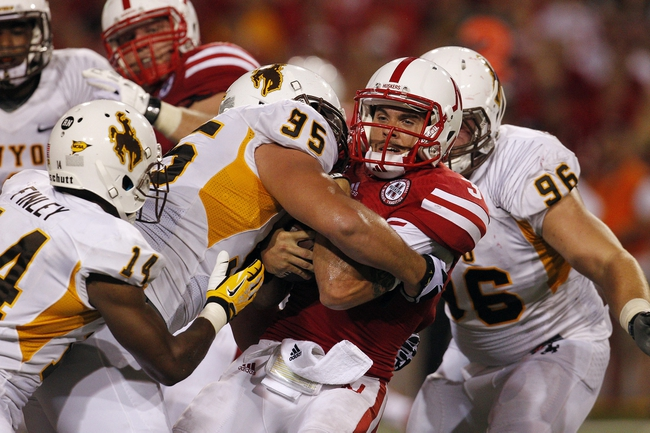Aug 31, 2013; Lincoln, NE, USA; Nebraska Cornhuskers quarterback Taylor Martinez (3) is tackled by Wyoming Cowboys defender Patrick Metens (95) in the second half at Memorial Stadium. Mandatory Credit: Bruce Thorson-USA TODAY Sports