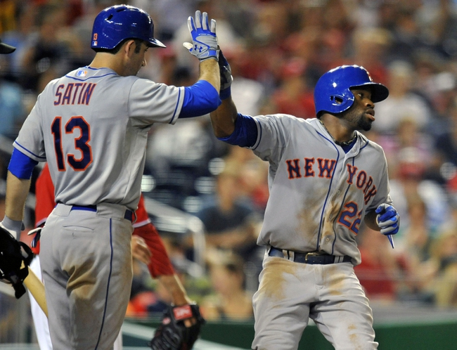 Aug 31, 2013; Washington, DC, USA; New York Mets left fielder Eric Young (22) is congratulated by Josh Satin (13) after scoring in the eighth inning against the Washington Nationals at Nationals Park. The Mets defeated the Nationals 11-3. Mandatory Credit: Joy R. Absalon-USA TODAY Sports