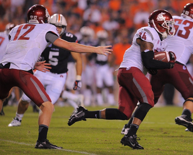 Aug 31, 2013; Auburn, AL, USA; Washington State Cougars quarterback Connor Halliday (12) hands off the ball to  running back Teondray Caldwell (34) at Jordan Hare Stadium. The Tigers defeated the Cougars 31-24. Mandatory Credit: Shanna Lockwood-USA TODAY Sports