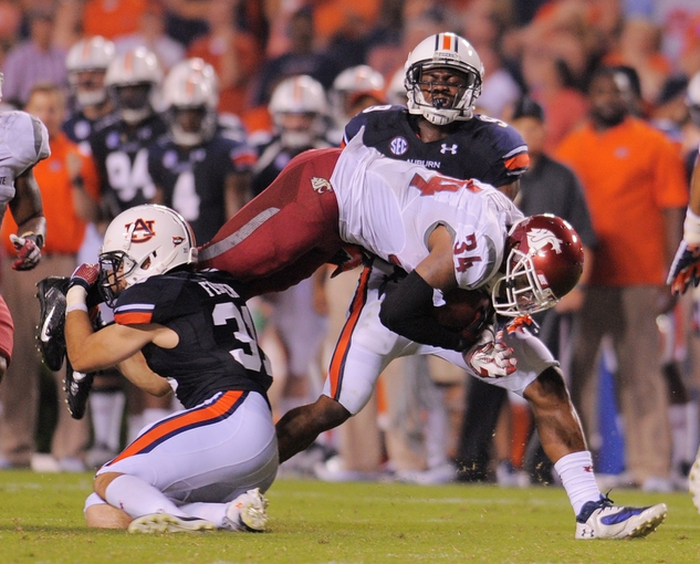 Aug 31, 2013; Auburn, AL, USA; Washington State Cougars running back Teondray Caldwell (34) tries to break past past Auburn Tigers defensive back Trent Fisher (31) at Jordan Hare Stadium. The Tigers defeated the Cougars 31-24. Mandatory Credit: Shanna Lockwood-USA TODAY Sports