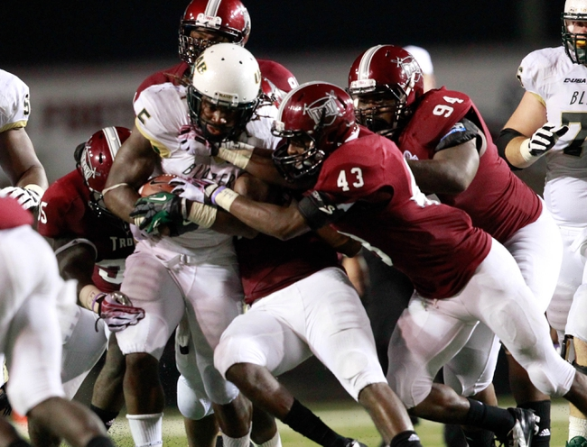 Aug 31, 2013; Troy, AL, USA;  UAB Blazers running back Darrin Reaves (5) is grabbed by Troy Trojan defenders at Veterans Memorial Stadium. The Trojans defeated the Blazers 34-31 in Overtime. Mandatory Credit: Marvin Gentry-USA TODAY Sports