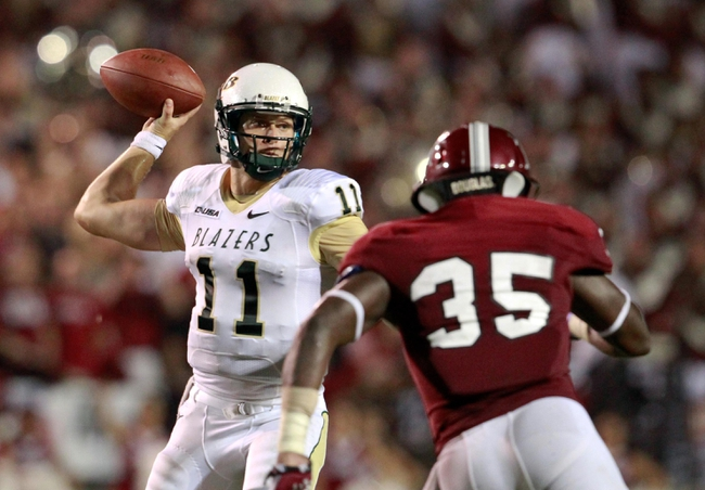 Aug 31, 2013; Troy, AL, USA;  UAB Blazers quarterback Austin Brown (11) passes as Troy Trojans linebacker Mark Wilson (35) defends at Veterans Memorial Stadium. The Trojans defeated the Blazers 34-31 in Overtime. Mandatory Credit: Marvin Gentry-USA TODAY Sports