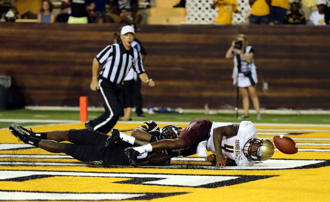 Aug 31, 2013; Hattiesburg, MS, USA; After a snap over his head, Texas State Bobcats quarterback Jordan Moore (4) knocks the football out of the end zone for a safety as he is hit by Southern Miss Golden Eagles defensive back Alex Smith (16) at M.M. Roberts Stadium.Texas State won 22-15. Mandatory Credit: Chuck Cook-USA TODAY Sports