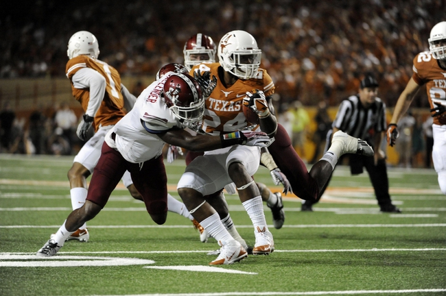 Aug 31, 2013; Austin, TX, USA; Texas Longhorns tailback Joe Bergeron (24) spins away from New Mexico State Aggies safety George Callender (5) during the second half at Darrell K Royal-Texas Memorial Stadium. Texas beat New Mexico State 56-7. Mandatory Credit: Brendan Maloney-USA TODAY Sports