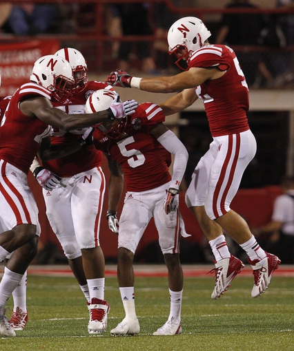 Aug 31, 2013; Lincoln, NE, USA; Nebraska Cornhuskers defender Josh Mitchell (5) celebrates his quarterback sack with Stanley Jean-Baptiste (16), Kevin Maurice (55) and Josh Banderas (52) against the Wyoming Cowboys in the second half at Memorial Stadium. Nebraska won 37-34. Mandatory Credit: Bruce Thorson-USA TODAY Sports