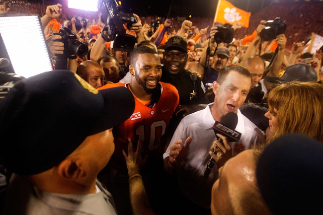 Aug 31, 2013; Clemson, SC, USA; Clemson Tigers head coach Dabo Swinney (right) and Clemson Tigers quarterback Tajh Boyd (10) are rushed by media following the game against the Georgia Bulldogs at Clemson Memorial Stadium. Tigers won 38-35. Mandatory Credit: Joshua S. Kelly-USA TODAY Sports