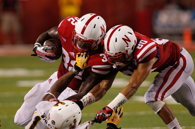 Aug 31, 2013; Lincoln, NE, USA; Wyoming Cowboys defender Darreon White (13) tackles Nebraska Cornhuskers running back Imani Cross (32) as Kenny Bell (80) tries to block in the second half at Memorial Stadium. Nebraska won 37-34. Mandatory Credit: Bruce Thorson-USA TODAY Sports
