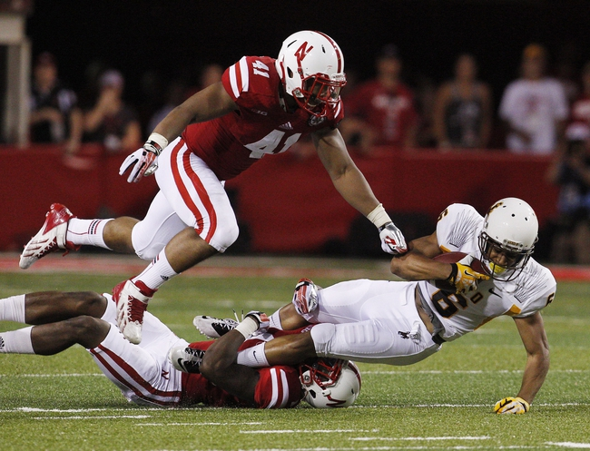 Aug 31, 2013; Lincoln, NE, USA; Nebraska Cornhuskers defenders David Santos (41) and Harvey Jackson (1) tackle Wyoming Cowboys receiver Robert Herron (6) in the first half at Memorial Stadium. Nebraska won 37-34. Mandatory Credit: Bruce Thorson-USA TODAY Sports