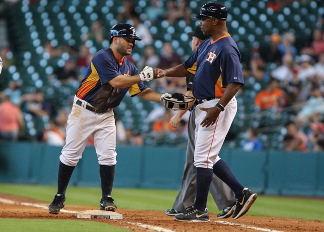 Sep 1, 2013; Houston, TX, USA; Houston Astros second baseman Jose Altuve (27) is congratulated by first base coach Dave Clark (35) after getting a single during the fifth inning against the Seattle Mariners at Minute Maid Park. Mandatory Credit: Troy Taormina-USA TODAY Sports
