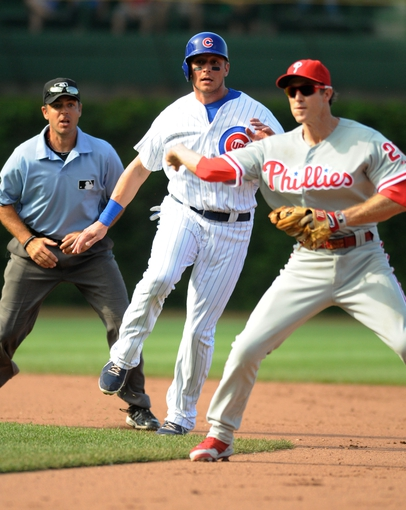 Sep 1, 2013; Chicago, IL, USA; Philadelphia Phillies second baseman Chase Utley (26) throws to first base after Chicago Cubs center fielder Ryan Sweeney (6) is called safe at second during the eighth inning at Wrigley Field. Mandatory Credit: Reid Compton-USA TODAY Sports