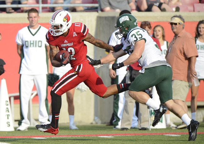 Sep 1, 2013; Louisville, KY, USA; Louisville Cardinals receiver Kai De La Cruz (12) breaks free from the attempted tackle of Ohio Bobcats safety Nathan Carpenter (35) during the second half of play at Papa John's Cardinal Stadium. Mandatory Credit: Jamie Rhodes-USA TODAY Sports