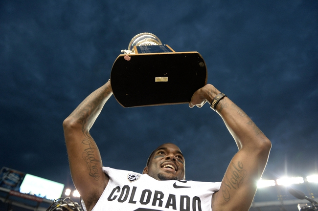 Sep 1, 2013; Denver, CO, USA; Colorado Buffaloes wide receiver Paul Richardson (6) holds the centennial cup following the win over the Colorado State Rams at Sports Authority Field at Mile High. The Buffaloes defeated the Rams 41-27. Mandatory Credit: Ron Chenoy-USA TODAY Sports