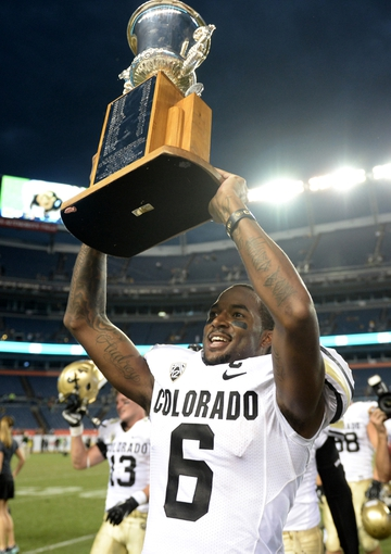Sep 1, 2013; Denver, CO, USA; Colorado Buffaloes wide receiver Paul Richardson (6) raises the centennial cup following the win over the Colorado State Rams at Sports Authority Field at Mile High. The Buffaloes defeated the Rams 41-27. Mandatory Credit: Ron Chenoy-USA TODAY Sports