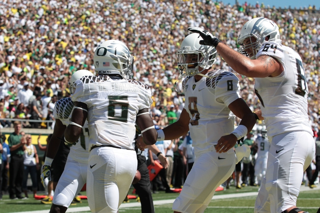 Aug 31, 2013; Eugene, OR, USA; Oregon Ducks offensive linesman Tyler Johnstone (64) and quarterback Marcus Mariota (8) celebrate running back De'Anthony Thomas (6) touchdown against the Nicholls State Colonels at Autzen Stadium. Mandatory Credit: Scott Olmos-USA TODAY Sports