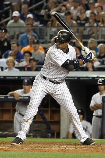 Aug 30, 2013; Bronx, NY, USA; New York Yankees second baseman Robinson Cano (24) bats against the Baltimore Orioles during a game at Yankee Stadium. Mandatory Credit: Brad Penner-USA TODAY Sports