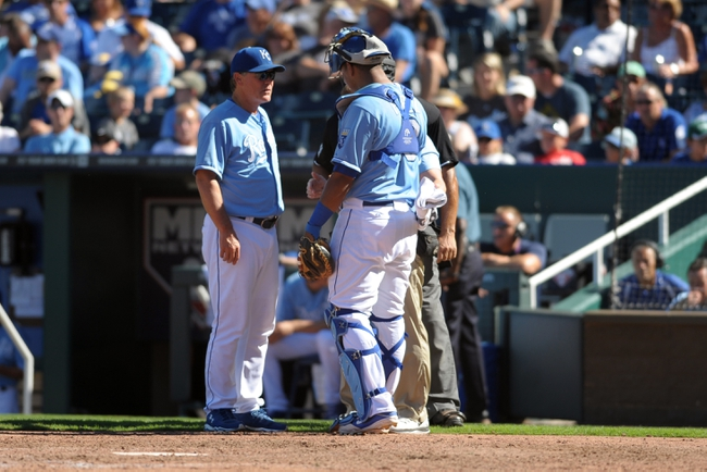 Sep 2, 2013; Kansas City, MO, USA; Kansas City Royals manager Ned Yost (3) checks out an injury to Kansas City Royals catcher Salvador Perez (13) in the ninth inning of the game against the Seattle Mariners at Kauffman Stadium. The Royals won 3-1. Mandatory Credit: Denny Medley-USA TODAY Sports