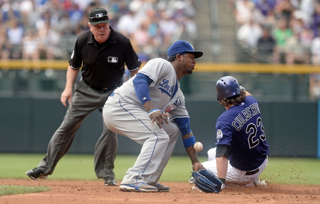 Sept 2, 2013; Denver, CO, USA; Colorado Rockies second baseman Charlie Culberson (23) reaches second base safe as Los Angeles Dodgers shortstop Hanley Ramirez (13) is unable to apply a tag as second base umpire Biran Gorman observes at Coors Field. Mandatory Credit: Ron Chenoy-USA TODAY Sports