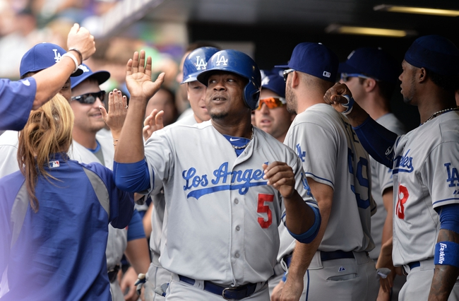 Sept 2, 2013; Denver, CO, USA; Los Angeles Dodgers third baseman Juan Uribe (5) is congratulated after coming into score in the fifth inning against the Colorado Rockies at Coors Field. Mandatory Credit: Ron Chenoy-USA TODAY Sports