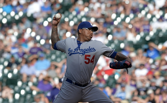 Sept 2, 2013; Denver, CO, USA; Los Angeles Dodgers relief pitcher Ronald Belisario (54) delivers a pitch in the eighth inning against the Colorado Rockies at Coors Field. The Dodgers defeated the Rockies 10-8. Mandatory Credit: Ron Chenoy-USA TODAY Sports
