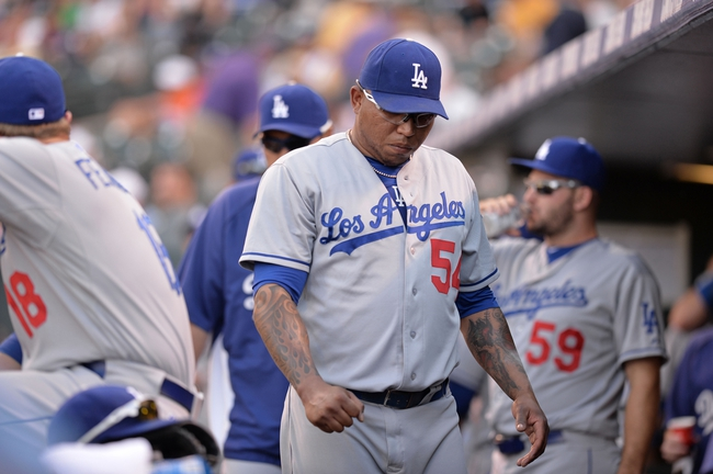 Sept 2, 2013; Denver, CO, USA; Los Angeles Dodgers relief pitcher Ronald Belisario (54) reacts to the end of the eighth inning against the Colorado Rockies at Coors Field. The Dodgers defeated the Rockies 10-8. Mandatory Credit: Ron Chenoy-USA TODAY Sports