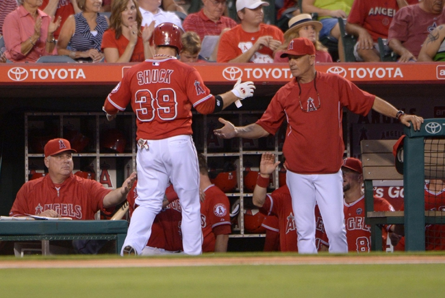Sep 1, 2013; Anaheim, CA, USA; Los Angeles Angels right fielder J.B. Shuck (39) is congratulated by manager Mike Scioscia (left) and bench coach Rob Picciolo after scoring in the third inning against the Tampa Bay Rays at Angel Stadium. Mandatory Credit: Kirby Lee-USA TODAY Sports
