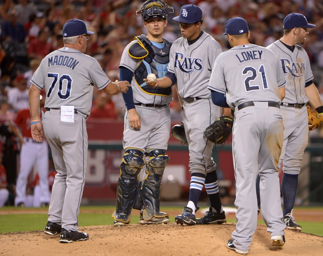 Sep 2, 2013; Anaheim, CA, USA; Tampa Bay Rays starter Chris Archer (22) is removed by managerJoe Maddon (70)  in the fourth inning as catcher Jose Lobaton (59), first baseman James Loney (21) and third baseman Evan Longoria (3) watch against the Los Angeles Angels at Angel Stadium. Mandatory Credit: Kirby Lee-USA TODAY Sports