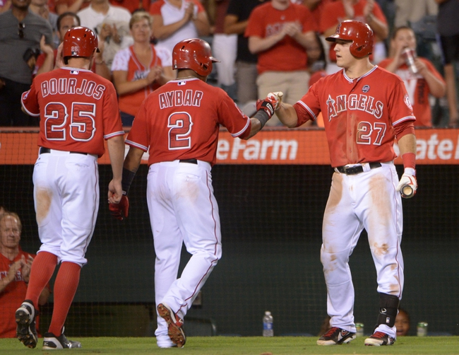 Sep 2, 2013; Anaheim, CA, USA; Los Angeles Angels shortstop Erick Aybar (2) and center fielder Peter Bourjos (25) are congratulated by left fielder Mike Trout (27) after scoring on a two-run home run by Aybar in the fourth inning against the Tampa Bay Rays at Angel Stadium. Mandatory Credit: Kirby Lee-USA TODAY Sports