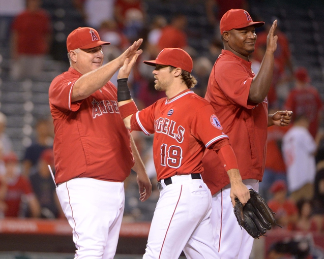 Sep 2, 2013; Anaheim, CA, USA; Los Angeles Angels manager Mike Scioscia (left) and outfielder Collin Cowgill (19) exchange high fives at the end of the game against the Tampa Bay Rays at Angel Stadium. The Angels defeated the Rays 11-2. Mandatory Credit: Kirby Lee-USA TODAY Sports