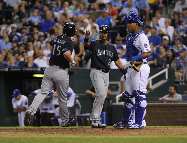 Sep 3, 2013; Kansas City, MO, USA; Seattle Mariners third baseman Kyle Seager (15) is congratulated by center fielder Franklin Gutierrez (21) after hitting a 2 run home run against the Kansas City Royals as Royals catcher Salvador Perez (13) looks on in the sixth inning at Kauffman Stadium. Mandatory Credit: John Rieger-USA TODAY Sports