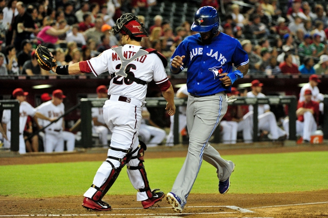Sept 3, 2013; Phoenix, AZ, USA; Toronto Blue Jays shortstop Jose Reyes (7) scores on a hit by third baseman Brett Lawrie (not pictured) as Arizona Diamondbacks catcher Miguel Montero (26) looks on during the first inning at Chase Field. Mandatory Credit: Matt Kartozian-USA TODAY Sports