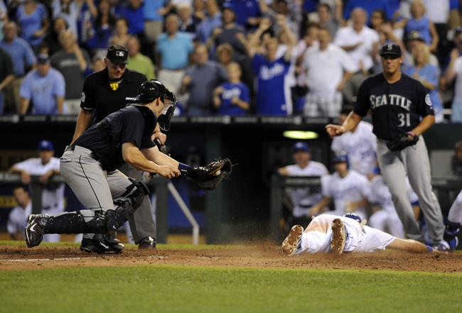 Sep 3, 2013; Kansas City, MO, USA; Kansas City Royals third baseman Mike Moustakas (8) scores the winning run past Seattle Mariners catcher Mike Zunino (3) in the eight inning at Kauffman Stadium. The Royals won the game 4-3. Mandatory Credit: John Rieger-USA TODAY Sports