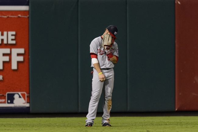 Sep 3, 2013; Philadelphia, PA, USA; Washington Nationals left fielder Bryce Harper (34) holds his mitt to his face after starting to come off the field after recording the second out of the eighth inning against the Philadelphia Phillies at Citizens Bank Park. The Nationals defeated the Phillies 9-6. Mandatory Credit: Howard Smith-USA TODAY Sports