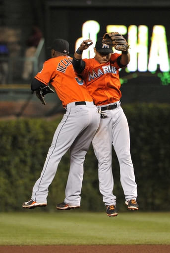 Sep 3, 2013; Chicago, IL, USA; Miami Marlins shortstop Adeiny Hechavarria (3) and second baseman Donovan Solano (17) celebrate they win against the Chicago Cubs at Wrigley Field. The Miami Marlins defeated the Chicago Cubs 6-2. Mandatory Credit: David Banks-USA TODAY Sports