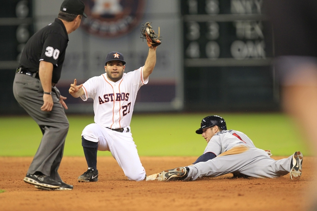 Sep 3, 2013; Houston, TX, USA; Houston Astros second baseman Jose Altuve (27) shows the ball to umpire Rob Drake (30) after tagging out Minnesota Twins left fielder Alex Presley (1) on a steal attempt during the tenth inning at Minute Maid Park. Mandatory Credit: Thomas Campbell-USA TODAY Sports