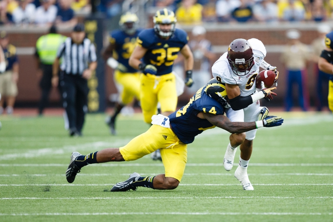 Aug 31, 2013; Ann Arbor, MI, USA; Michigan Wolverines safety Josh Furman (14) goes after Central Michigan Chippewas wide receiver Andrew Flory (9) at Michigan Stadium. Mandatory Credit: Rick Osentoski-USA TODAY Sports