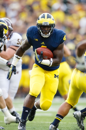 Aug 31, 2013; Ann Arbor, MI, USA; Michigan Wolverines running back De'Veon Smith (4) runs the ball during the second half against the Central Michigan Chippewas at Michigan Stadium. Mandatory Credit: Rick Osentoski-USA TODAY Sports