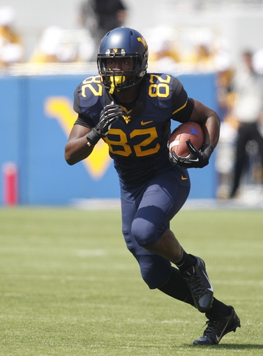 Aug 31, 2013; Morgantown, WV, USA; West Virginia Mountaineers wide receiver Devonte Mathis (82) runs after a pass reception against the William & Mary Tribe during the third quarter at Milan Puskar Stadium. The West Virginia Mountaineers won 24-17. Mandatory Credit: Charles LeClaire-USA TODAY Sports