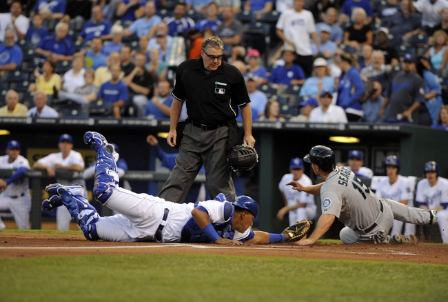 Sep 4, 2013; Kansas City, MO, USA; Seattle Mariners third baseman Kyle Seager (15) is tagged out at home by Kansas City Royals catcher Salvador Perez (13) in the first inning at Kauffman Stadium. Mandatory Credit: John Rieger-USA TODAY Sports