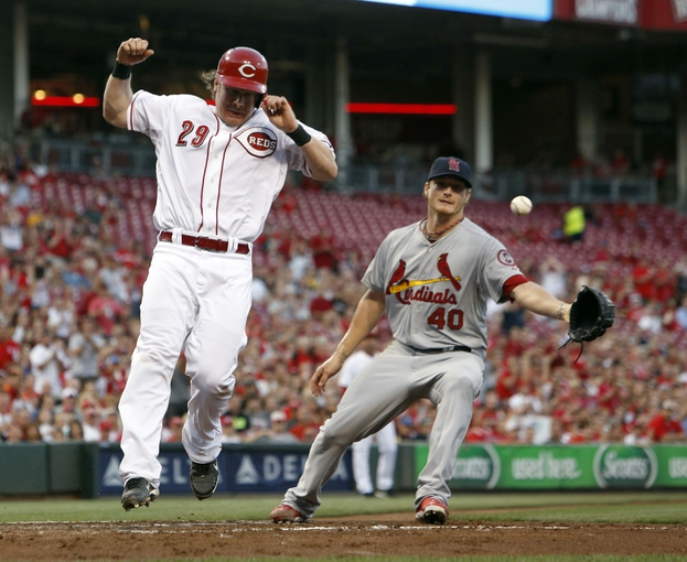 Sep 4, 2013; Cincinnati, OH, USA; Cincinnati Reds catcher Ryan Hanigan (29) scores at home after a wild pitch from St. Louis Cardinals starting pitcher Shelby Miller (40) in the second inning at Great American Ball Park. Mandatory Credit: David Kohl-USA TODAY Sports